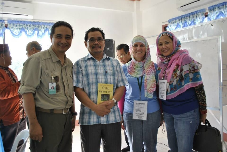 Dann Pantoja (President, PeaceBuilders Community, Inc.), Mohagher Iqbal (Chairman, MILF Peace Panel), Wendy Kroeker (Senior Consultant, PeaceBuilders Community, Inc.), and Joji Pantoja (Chief Operating Officer, Coffee For Peace, Inc.) pose for a picture during the PCEC-MILF meeting last May 2013 in Barangay Simuay, Municipality of Sultan Kudarat, Province of Maguindanao. Chairman Iqbal shows his book, Conflict Transformation, by John Paul Lederach. Bishop Efraim Tendero (National Director, Philippine Council of Evangelical Churches) is at the background, comparing notes with other MILF leaders.
